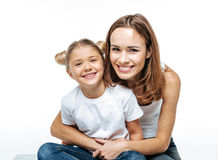 Smiling mother hugging daughter royalty free stock images