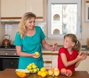 Smiling mother with keeping sweet pear daughter. Healthy eating - woman and child in the kitchen with different kinds of fruits