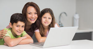 Smiling mother with kids using laptop in kitchen Royalty Free Stock Photography