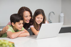 Smiling mother with kids using laptop in kitchen Stock Image