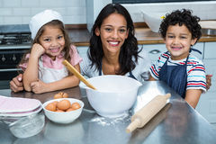 Smiling mother in the kitchen with her children. Portrait of smiling mother in the kitchen with her children Stock Photography