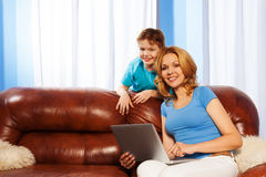Smiling mother with laptop and her son together Royalty Free Stock Photography