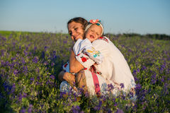 Smiling mother and little daughter on nature in a field Stock Images