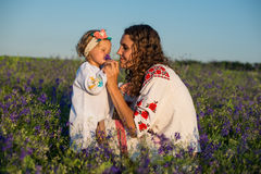 Smiling mother and little daughter on nature in a field of poppies, girl is holding flowers Royalty Free Stock Images