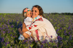 Smiling mother and little daughter on nature in a field of poppies, girl is holding flowers. Stock Images