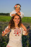 Smiling mother and little daughter on nature in a field of poppies, girl is holding flowers. Stock Image
