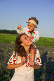 Smiling mother and little daughter on nature in a field of poppies, girl is holding flowers. Stock Photo