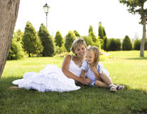 Smiling mother and little daughter on nature. Happy people outdoors Stock Photos