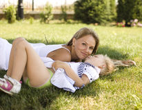 Smiling mother and little daughter on nature. Happy people outdoors Stock Photo
