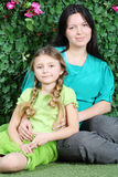 Smiling mother and little daughter sit on lawn in garden Royalty Free Stock Images