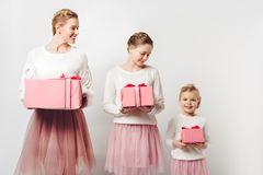 Smiling mother and little daughters in similar pink tutu tulle skirts with wrapped gifts. On grey stock images