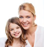Smiling mother and little girl at home. Family, child and home concept - smiling mother and little girl at home Royalty Free Stock Photo