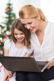 Smiling mother and little girl laptop computer. Family, childhood, holidays, technology and people - smiling mother and little girl with laptop computer over Royalty Free Stock Photography