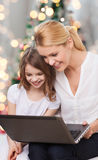 Smiling mother and little girl with laptop Royalty Free Stock Photography