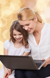 Smiling mother and little girl with laptop Stock Image