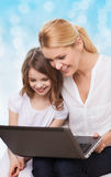 Smiling mother and little girl with laptop. Family, childhood, holidays, technology and people concept - smiling mother and little girl with laptop computer over Stock Photo