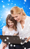 Smiling mother and little girl with laptop. Family, childhood, holidays, technology and people concept - smiling mother and little girl with laptop computer over Royalty Free Stock Images