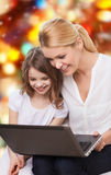 Smiling mother and little girl with laptop. Family, childhood, holidays, technology and people concept - smiling mother and little girl with laptop computer over Stock Image