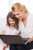 Smiling mother and little girl with laptop at home Stock Photography