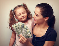 Smiling mother looking on happy daughter holding cash of dollars Stock Images