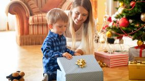 Beautiful smiling mother looking at her boy opening Christmas gifts and presents stock photos
