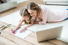 Smiling mother looking how concentrated daughter drawing Stock Image