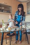 smiling mother looking how son holding dough royalty free stock image