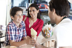 Smiling Mother Looking At Son Receiving Ice Cream From Waiter Royalty Free Stock Photography