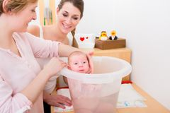 Mother looking at woman bathing her baby stock photography
