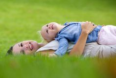 Smiling mother lying down on grass with cute baby. Side view portrait of a smiling mother lying down on grass with cute baby stock photo