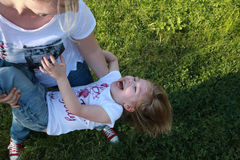 Smiling mother plays with her child on grass Stock Photos