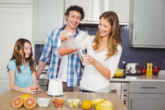 Smiling mother pouring fruit juice in glass with family Stock Photography