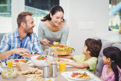 Smiling mother serving food to children Stock Photo