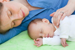 Smiling mother sleeping with her newborn baby Stock Photos
