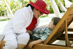 Smiling mother and son. Woman smiling at a boy who is sitting on an outdoor lounge chair in tropical vacation setting, caucasian/white Stock Image