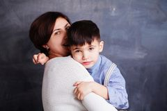 Smiling mother and son cuddling on chalkboard background. Cute little boy child and woman portrait stock photography