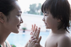 Smiling mother and son face to face and holding hands by the pool Royalty Free Stock Photo