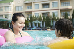 Smiling mother and son floating on inflatable tubes and playing in the pool Stock Photos