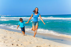 Smiling mother and son hold arms while running Stock Photos