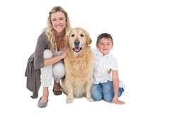 Smiling mother and son petting their golden retriever Royalty Free Stock Images
