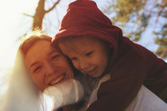 Smiling mother and son playing together in park. Portrait of smiling mother and son playing together in park. Little son hugging his young mom, having fun Royalty Free Stock Images