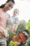 Smiling mother and son pointing and looking at a butterfly in the garden Stock Photo