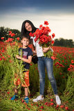 Smiling mother and son posing on the poppy field Stock Photography