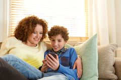 Smiling mother and son relaxing at home Royalty Free Stock Photo