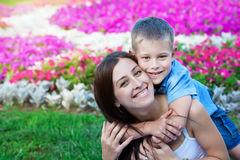 Smiling Mother and son siting on grass Royalty Free Stock Photos