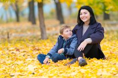 Smiling mother and son sitting in fall leaves. stock photography