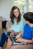 Smiling mother and son sitting on sofa using laptop in living room. At home Royalty Free Stock Photos