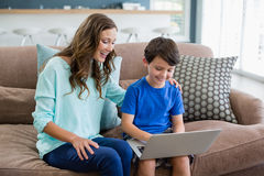 Smiling mother and son sitting on sofa using laptop in living room. At home Stock Photos