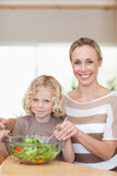 Smiling mother and son stirring salad Stock Image