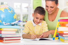 Smiling mother and son studying Royalty Free Stock Photography